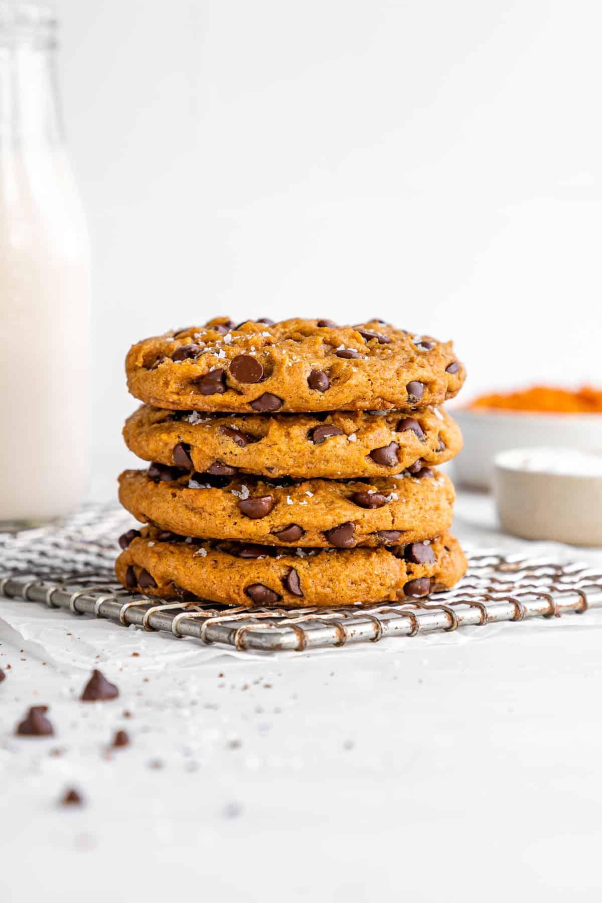 a stack of vegan pumpkin chocolate chip cookies on a metal cooling rack