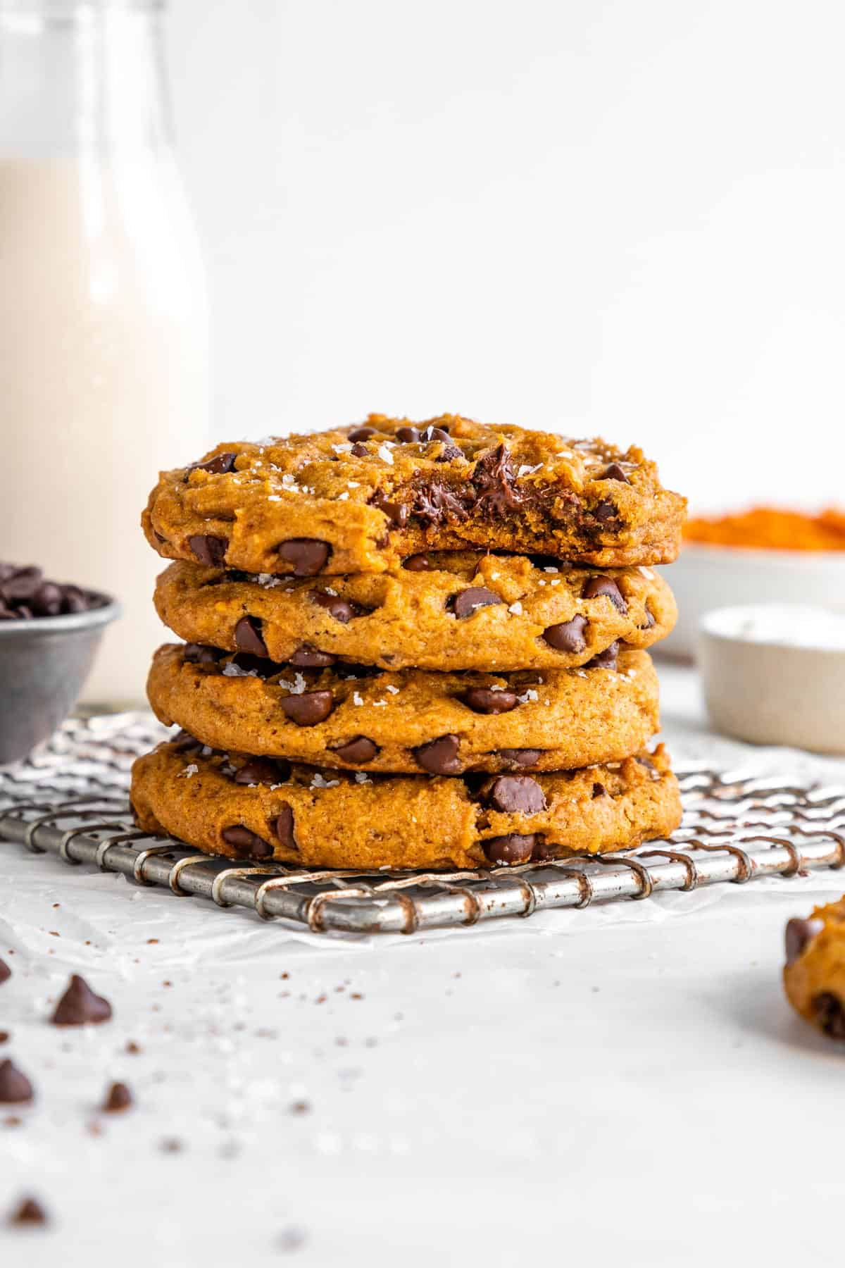 a stack of vegan pumpkin chocolate chip cookies with a bite taken out of the top cookie