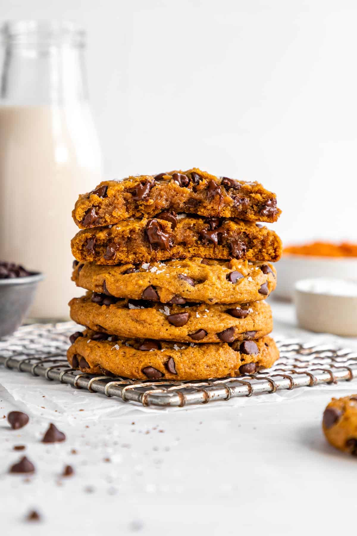 vegan pumpkin chocolate chip cookies stacked on top of each other with the top two cookies sliced in half