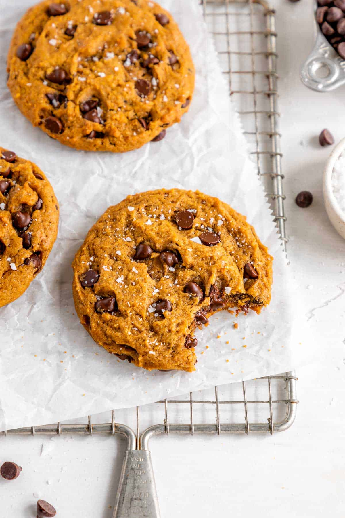 vegan pumpkin chocolate chip cookies on a cooling rack with a bite taken out of the middle cookie