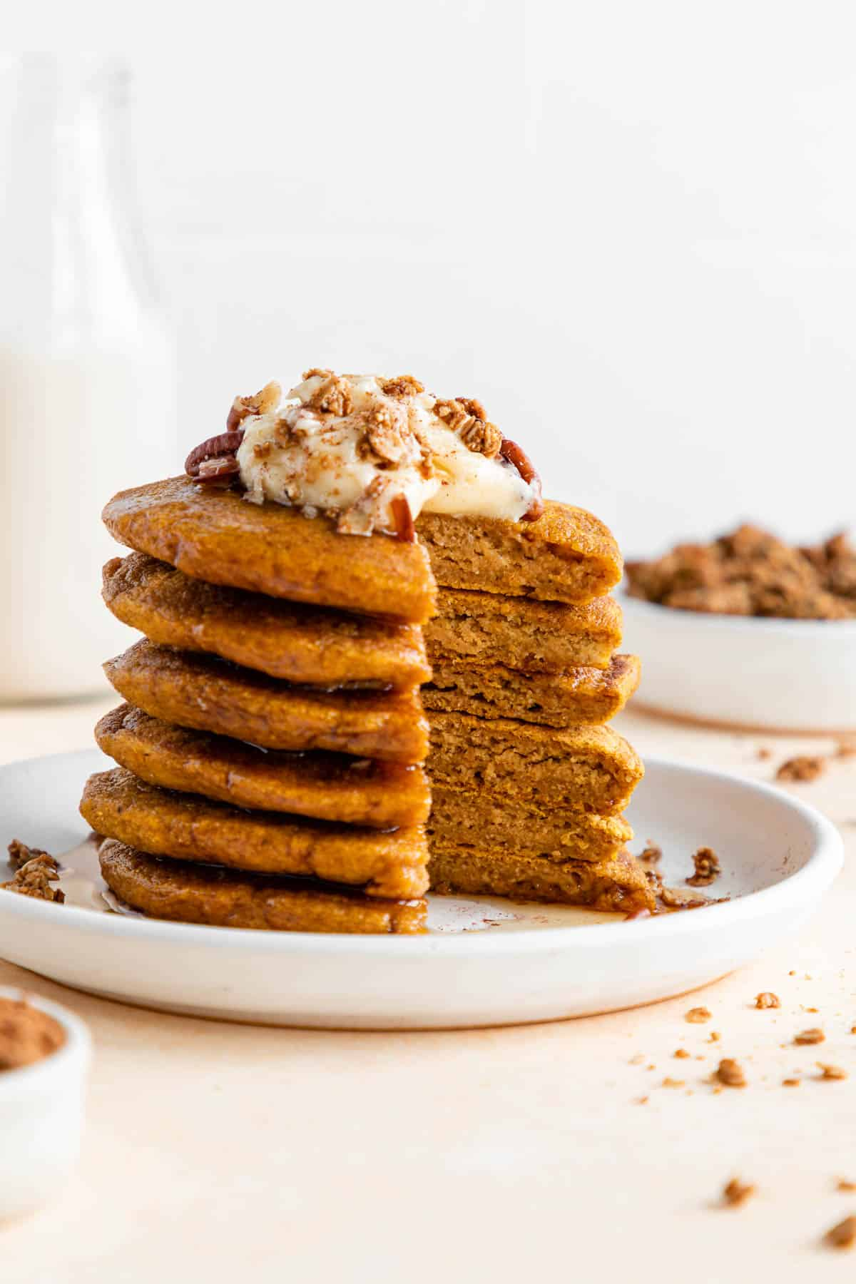 a sliced stack of vegan pumpkin pancakes on a plate with frosting and maple syrup
