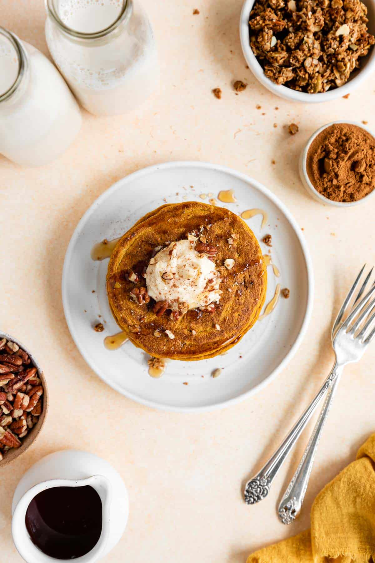 overhead image of vegan pumpkin pancakes stacked on a plate with whipped cream on top