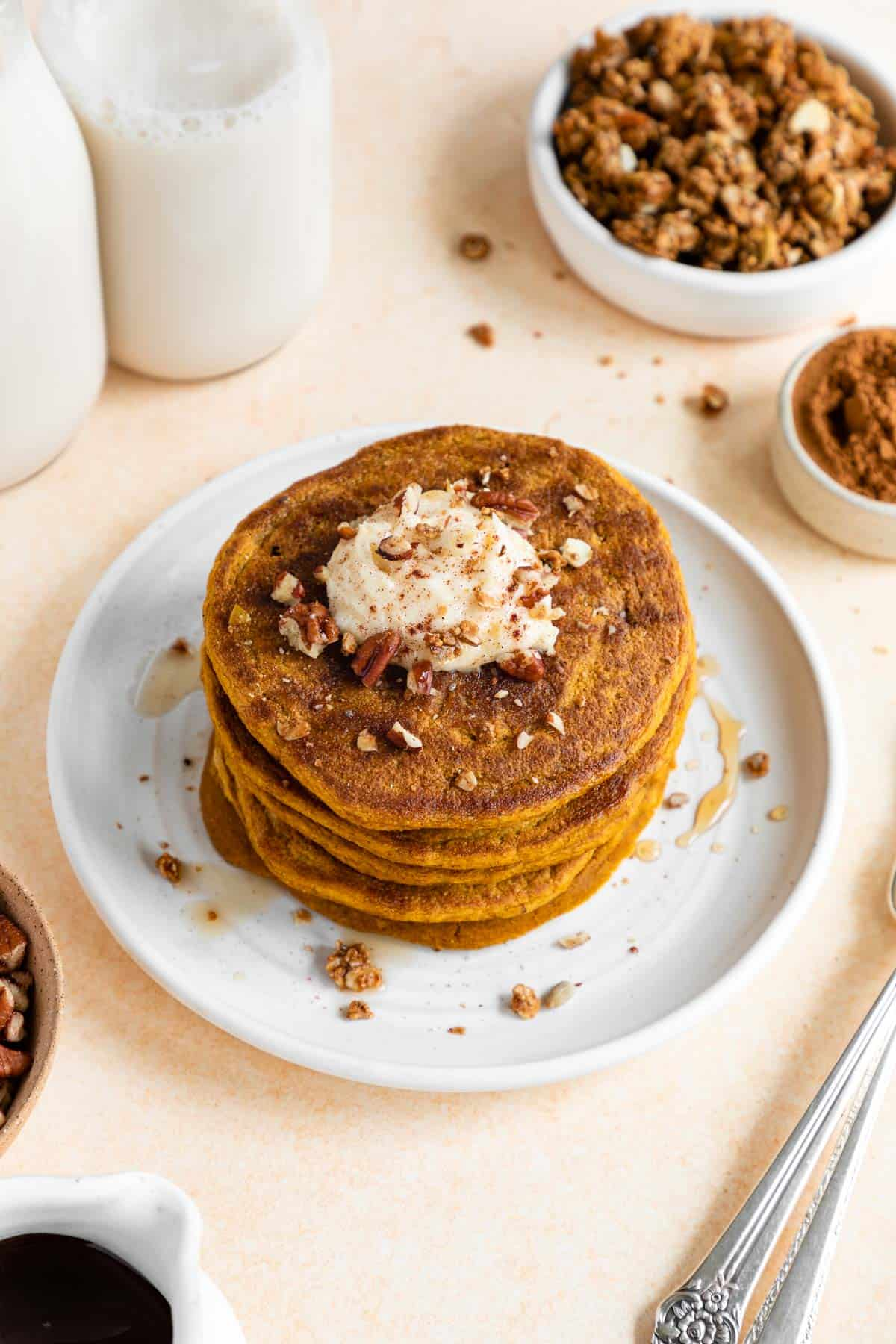 vegan pumpkin pancakes on a plate with whipped cream, maple syrup, and pecans on top