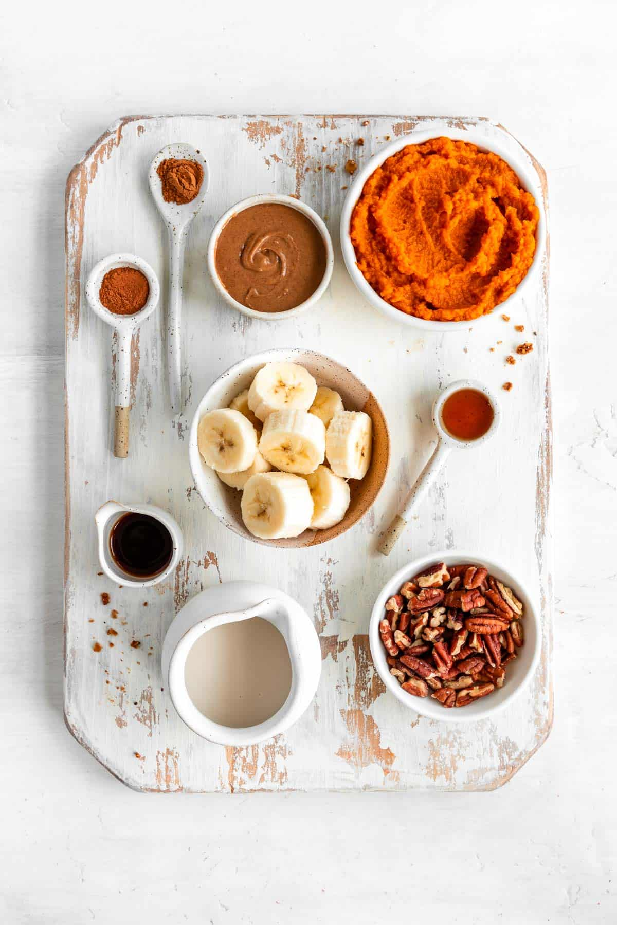 a distressed wood cutting board topped with bowls of pumpkin puree, banana, pecans, oat milk, almond butter, cinnamon, maple syrup, and vanilla