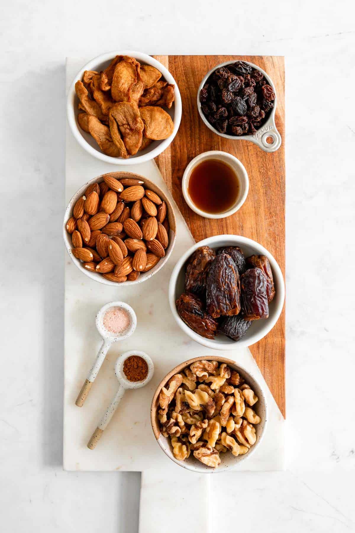 a serving board with bowls of almonds, walnuts, medjool dates, soft dried apples, raisins, cinnamon, vanilla, and salt