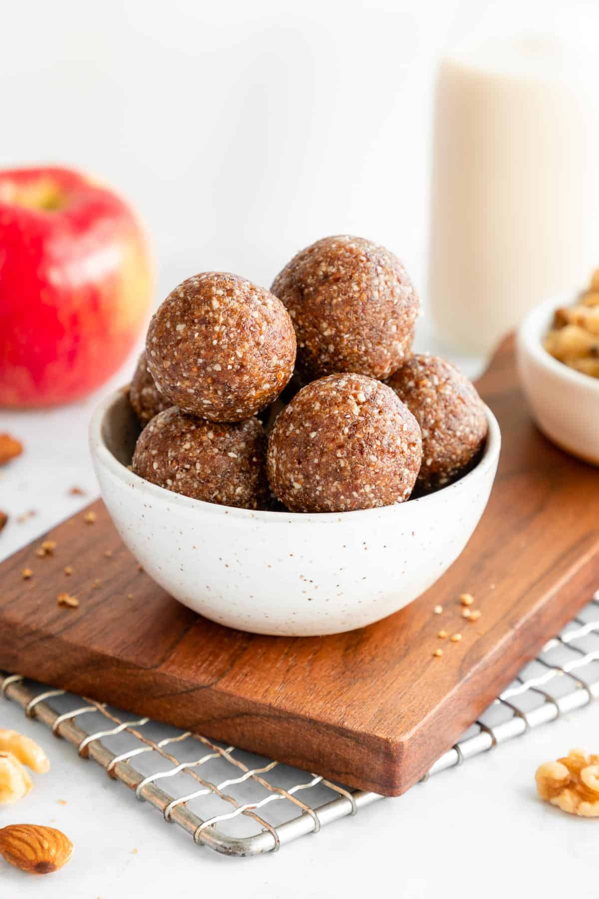 a stack of apple pie energy balls inside a small ceramic bowl