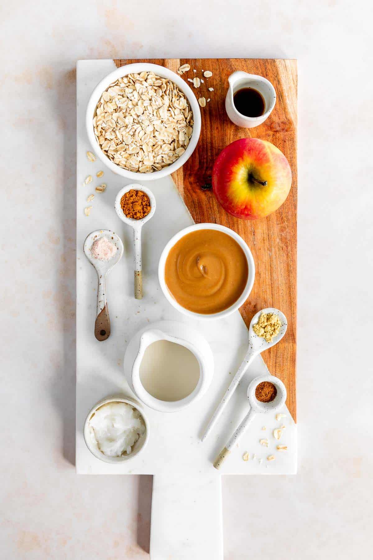 a marble serving board with bowls of rolled oats, vegan caramel sauce, honey crisp apple, oat milk, cinnamon, nutmeg, vanilla extract, and salt