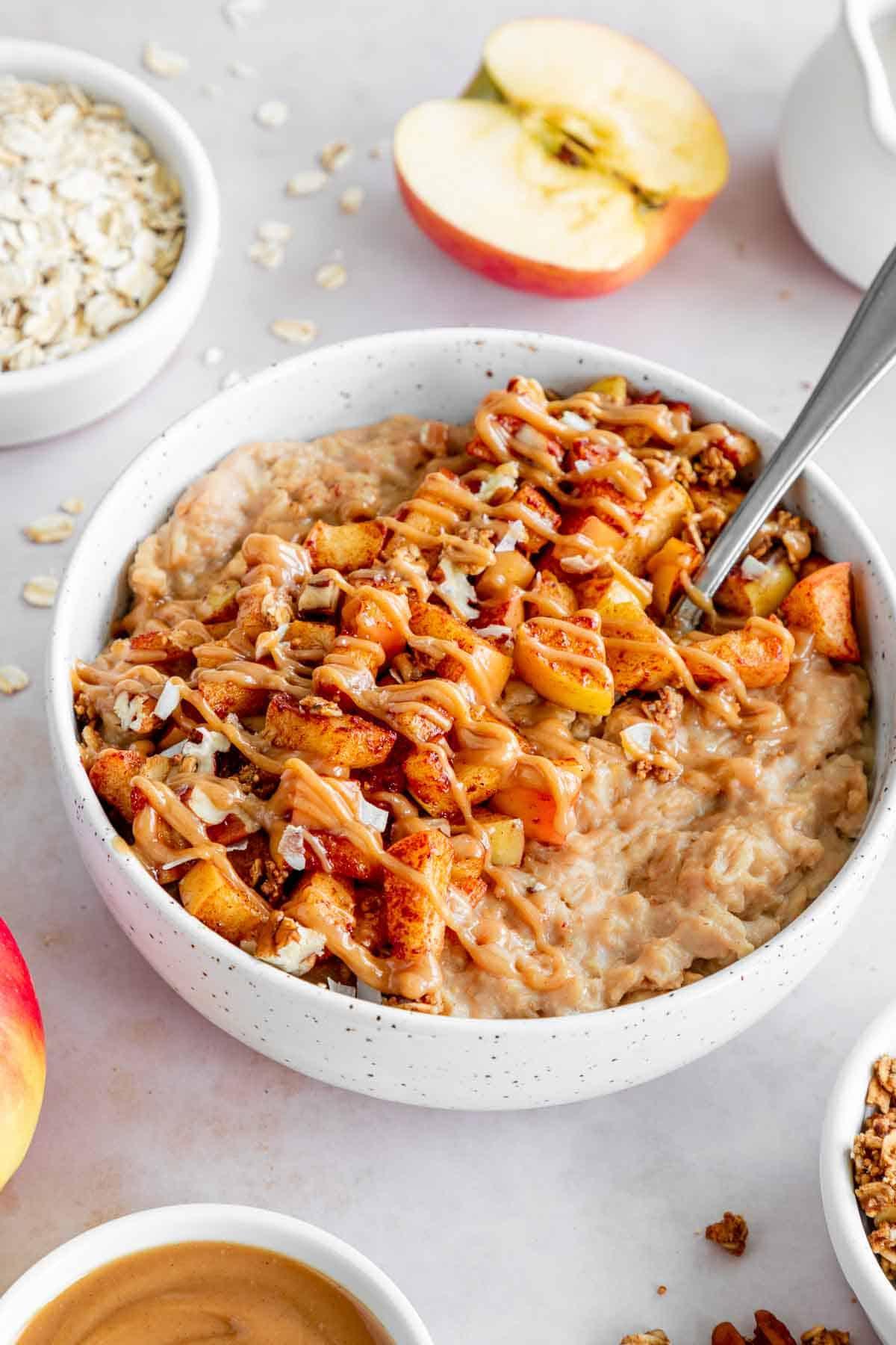 a bowl of vegan caramel apple oatmeal with pecans, diced honey crisp apples, cinnamon, and granola on top