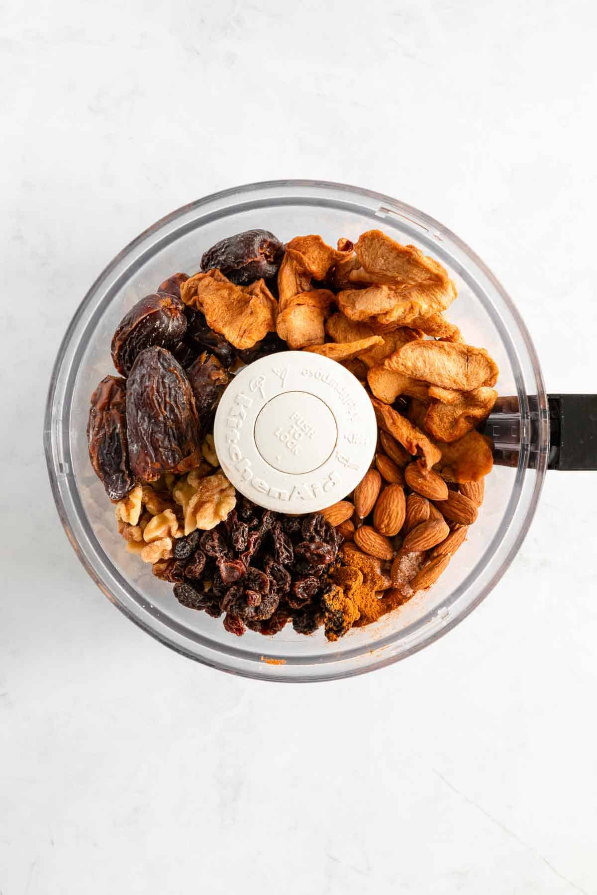 medjool dates, almonds, walnuts, dried apples, and raisins inside a food processor bowl